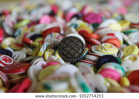 a beautiful collection of a lot of colorful buttons, spread randomly, with a brown button at the center of all attention