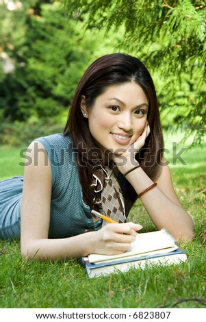 A beautiful college student studying outdoor in the park
