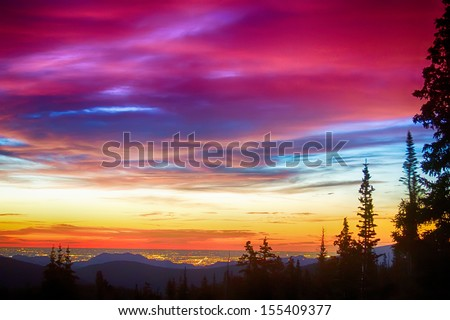 A beautiful colorful epic sunrise over the city lights of Boulder Colorado looking out from high up on the Rocky Mountains Rollins Pass and the Continental Divide west of Boulder.