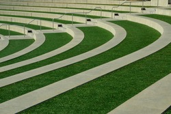 A beautiful concrete and green grass curvy stadium in the park