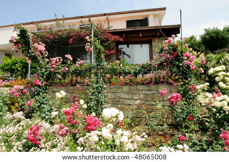 Cvijeće oko kuće  Stock-photo-a-beautiful-country-house-surrounded-by-a-garden-full-of-flowers-48065008