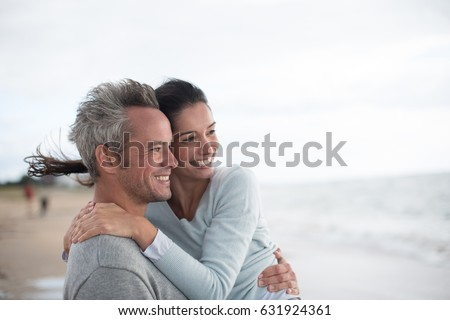 A beautiful couple in their forties walks on the beach, the gray-haired man carries the woman in his arms. They wear sweaters and jeans