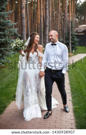 A beautiful couple of newlyweds are walking in a pine park. The bride in a chic dress holds a bouquet in her hands and looks at the groom, laughing. He closed his eyes and laughs too #1430938907