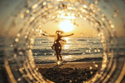 A beautiful creative composition of a sea landscape shot through a circle focus showing a young woman who is having fun on the beach in sunset.