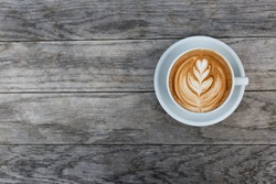 A beautiful cup of cappuccino with latte art in the wooden space background. Trendy toning. Minimal composition, hipster vibes. Top view, flat lay copy space for your text.