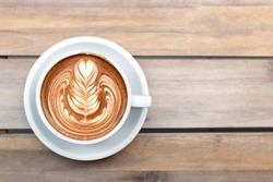 A beautiful cup of cappuccino with trendy latte art in the wooden space background. Minimal composition, hipster vibes. Top view, flat-lay. Copy space for your text.
