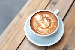 A beautiful cup of cappuccino with trendy latte art in the wooden space background. Minimal composition, hipster vibes. Side view. Copy space for your text.