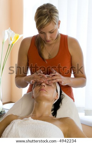 A beautiful dark haired woman receives a facial treatment from a young blond beautician