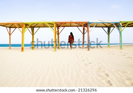 a beautiful dark haired woman walks underneath some colorful wooden canopies along a stunning sandy beach in the cape Verde islands