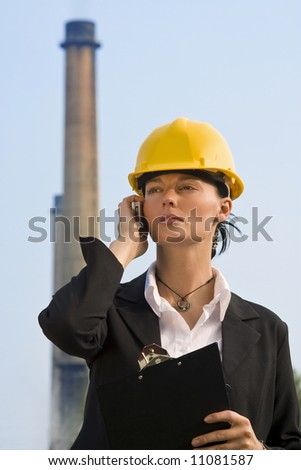 A beautiful dark haired woman wearing a hard hat and talking on her mobile phone while standing in front of a factory and its chimneys