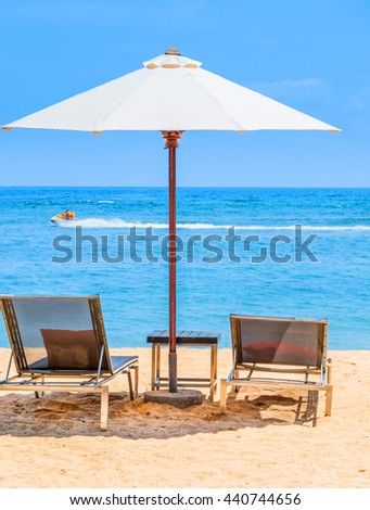 A beautiful day at the beach with sun lounger chairs under an umbrella and a Jet Ski zooming past in the distance. #440744656