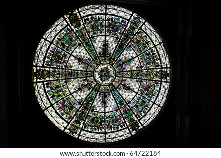 A beautiful delicately assembled stained glass round window in ceiling.