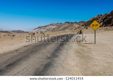 A beautiful Desert Road Landscape with blue sky and DIP sign on the roadside