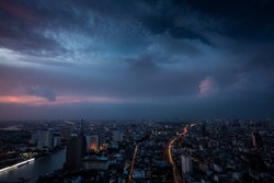 A beautiful dramatic dark pink and blue sky before a storm comes over Bangkok in Thailand at night with street lights and a river on the left side during night with the city shining