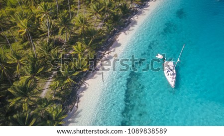 A beautiful drone shot of a white sailing yacht anchoring in crystal clear turquoise water right next to the perfect white sand beach of a tropical island in the caribbean San Blas Islands of Panama.