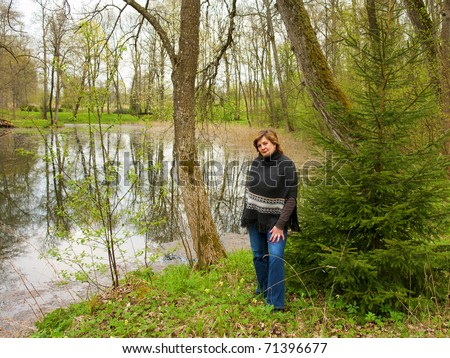 A beautiful elderly lady on the shore of the pond