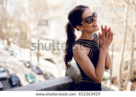 A beautiful,elegant brunette in black sunglasses, sexy black dress, hair ponytail and special features, smiles adorably and looks at one side with hands close to face.Horizontal view on the balcony.