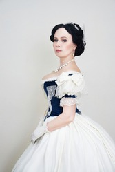 A beautiful elegant dark haired woman in a historic 1867 coronation dress on a white background looks at the camera