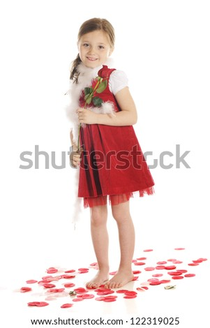 A beautiful elementary girl holding a long-stemmed rosebud while standing barefoot among rose petals.  She dressed in red with a fluffy, white boa.  On a white background.