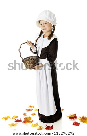 A beautiful elementary Pilgrim girl holding a basketful of the acorns she's collected.  She's surrounded by colorful fall leaves.  On a white background.