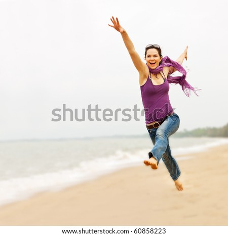 A beautiful energetic young woman taking a great leap on the beach - stock photo