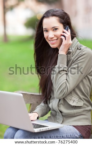 A beautiful ethnic college student talking on the phone working on her laptop on campus