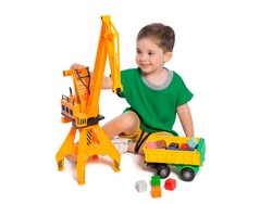 A beautiful European boy plays with a crane on a white background. The child is 2.5 years old. The development and education of children of preschool age.