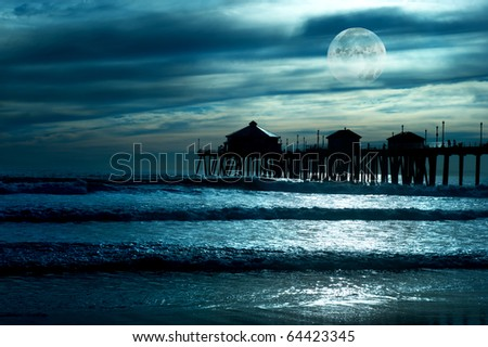 A beautiful evening along the beach shows a pier during a low moon with reflections in the water, and a moody sky.