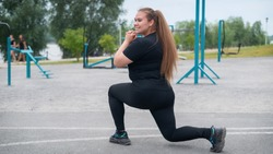 A beautiful fat girl in a black tracksuit is engaged in fitness on the sports ground. Young woman lunges outdoors on a warm summer day. Healthy lifestyle and weight loss.
