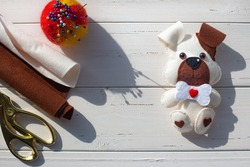 A beautiful felt puppy with a brown ear and muzzle, with a bone and a red  heart on a white boards background. Tailoring scissors, pins, pincushion. Creativity, hobbies, sewing toys with the child.
