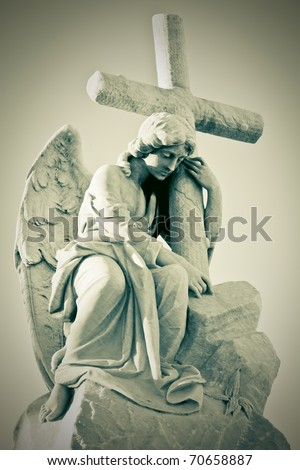A beautiful female angel holding a christian cross with a vintage photo look