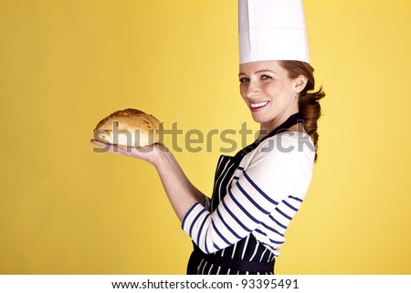 A beautiful female baker showing of a freshly baked loaf of bread. Home made bread.