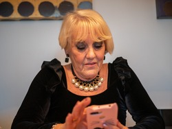 A beautiful female in a black elegant dress and pearl neckless using a smartphone