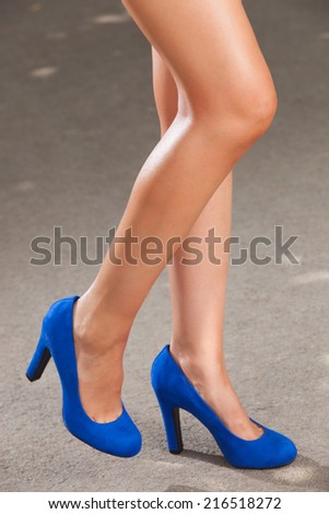 A beautiful female legs with blue shoes