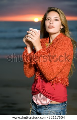 A beautiful female model standing on the beach at sunset drinking coffee
