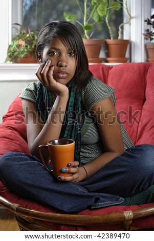 A beautiful female relaxing in her home drinking tea or coffee.