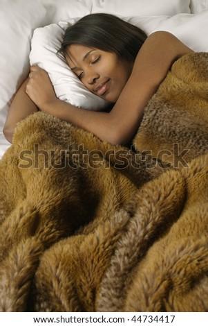 A beautiful female sleeping comfortably under warm blankets.