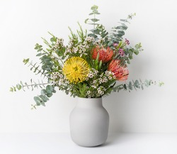 A beautiful floral arrangement of Australian native red and yellow Waratah flowers,  eucalyptus leaves and wax flowers in a stylish grey vase, with a white background.