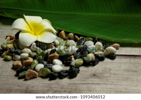 A beautiful flower with banana leaf and tiny stones on wooden background. Concept of spa,relaxation,rest,pampered,zen. #1093406012