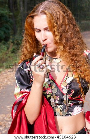 A beautiful ginger-haired girl in gypsy suit with pipe