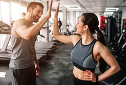 A beautiful girl and her well-built boyfriend are greeting each other with a high-five. They are happy to see each othr in the gym. Young people are ready to start their workout.