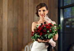 A beautiful girl-bride in a white wedding dress and white gloves with a huge bouquet of roses stands on the background of a wooden wall by the window and smiles. Hairstyle and bright red lipstick