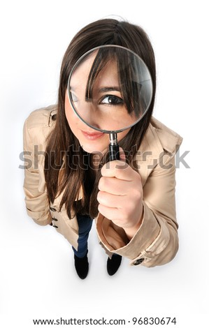 a beautiful girl holds a magnifying lens