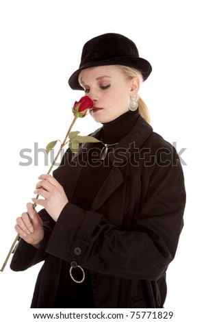 a beautiful girl in a black hat and coat smelling a red rose.