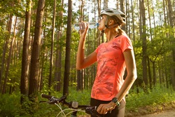A beautiful girl in a bright orange t-shirt, shorts and helmet drinks water after a bike ride in the forest