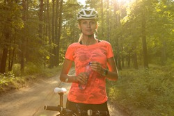 A beautiful girl in a bright orange t-shirt, shorts and helmet holds a bottle of water after a bike ride in the forest