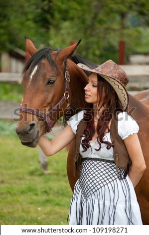 A beautiful  girl in a cowboy hat with a horse