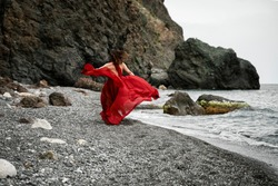 A beautiful girl in a long red dress that flutters in the wind, runs along the beach with the concept of femininity, harmony. Black rocks and rocks on the shore