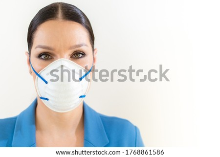 A beautiful girl in a medical mask on her face is photographed in the studio. Coronavirus and Covid-19 Protection