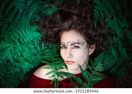 A beautiful girl in a red dress lies on the fern leaves. Looking into the camera. Striking appearance.